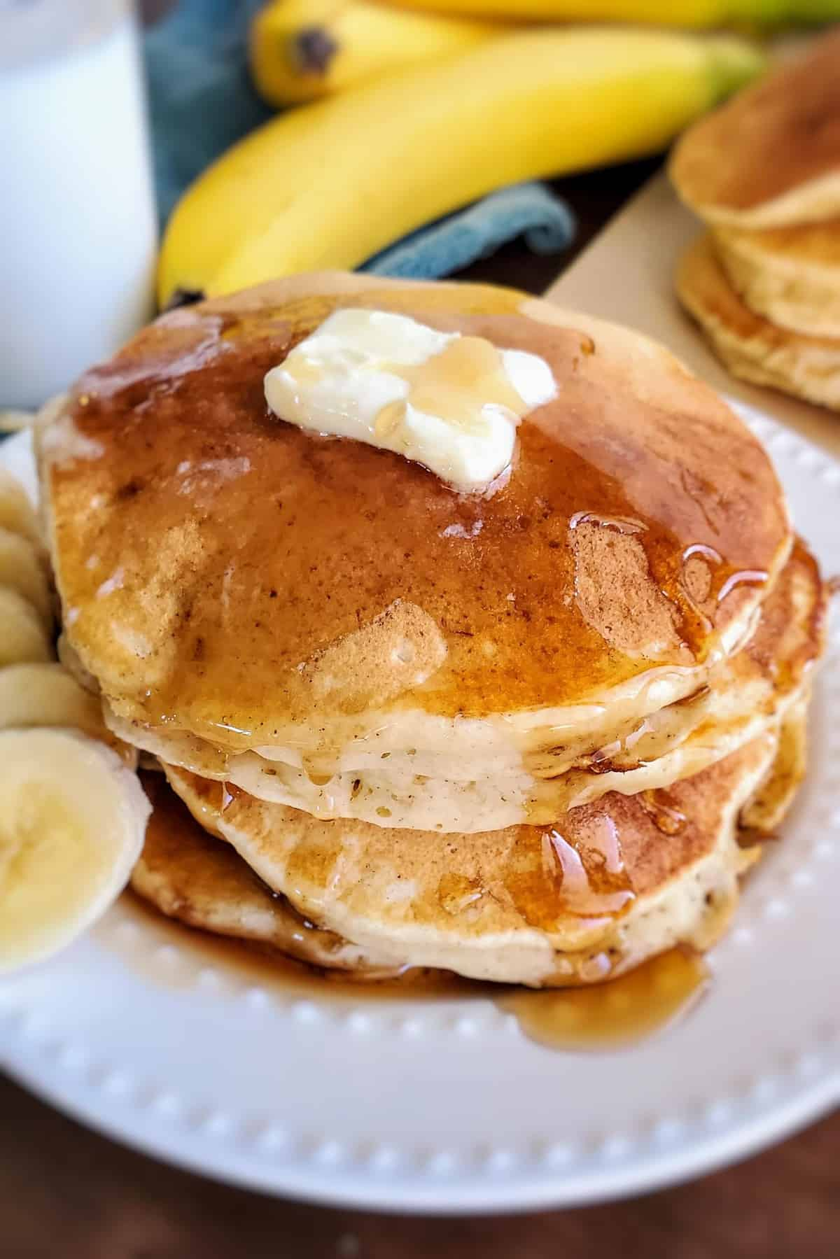 Pancakes with a pat of butter on top, dripping with syrup.