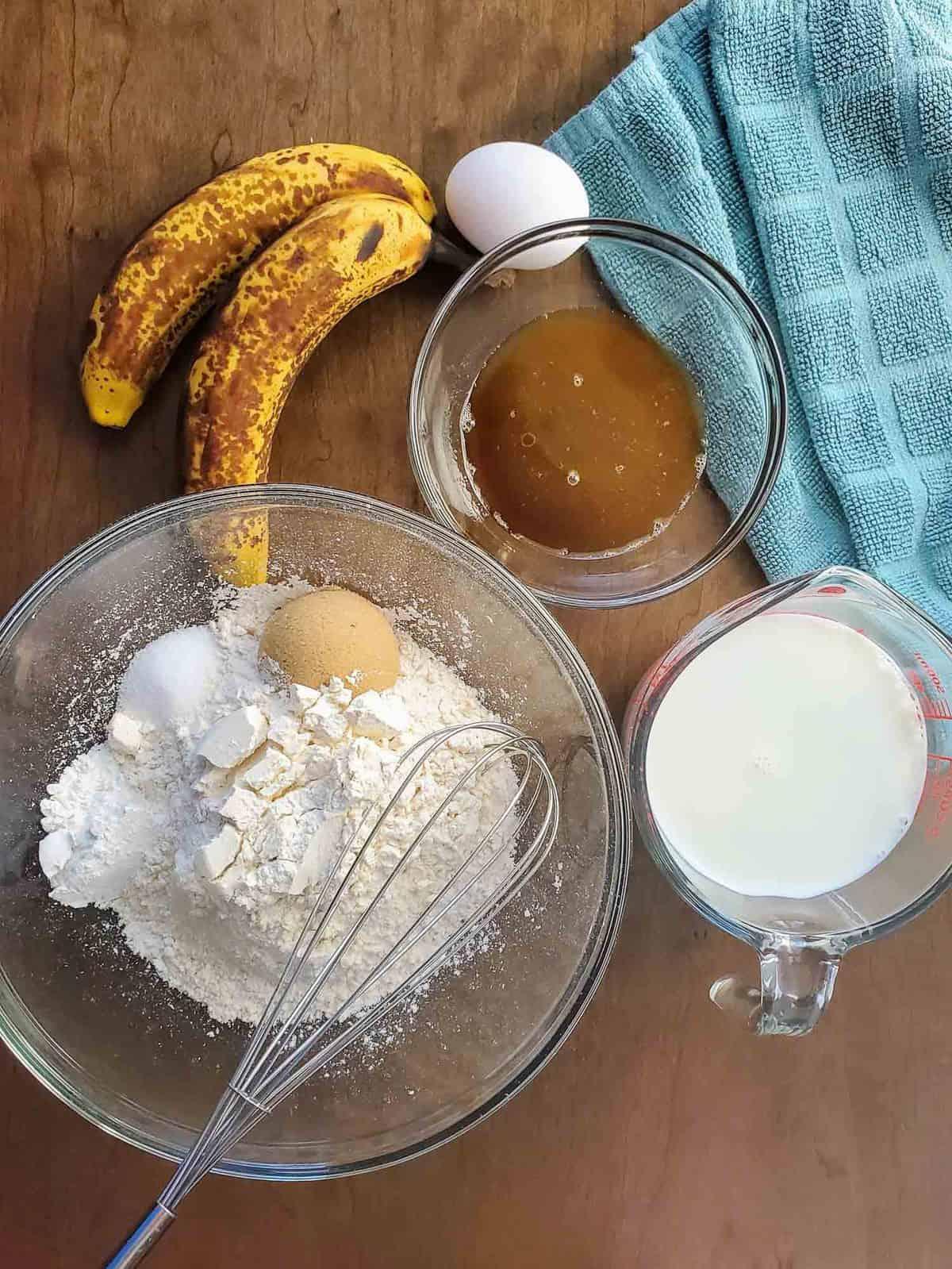 Overhead view of ingredients: flour, egg, brown sugar, banana, milk.