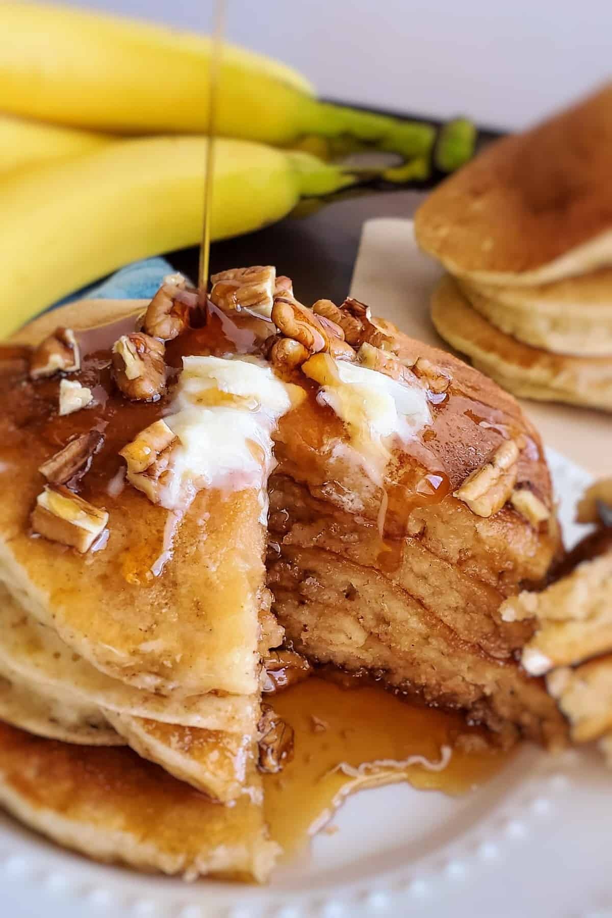 Syrup being poured on a stack of pancakes topped with nuts and butter.