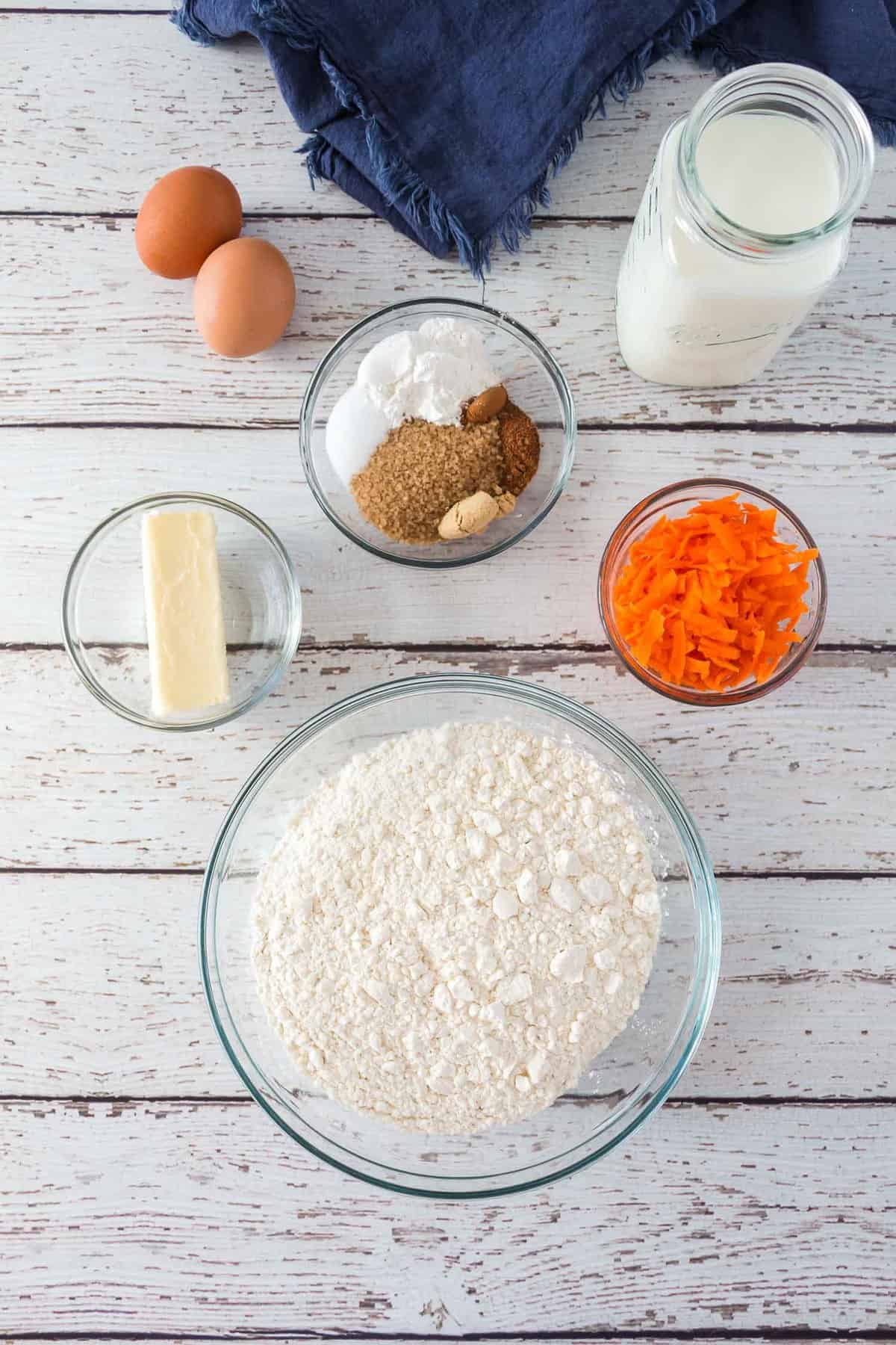 Overhead view of ingredients: Flour, carrots, milk, eggs, spices. sugar.