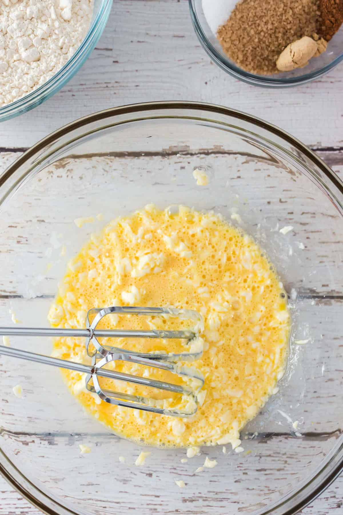 Eggs and butter beat together in a bowl.