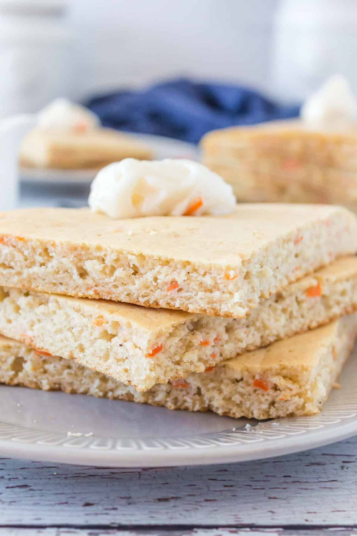 Carrot pancakes cut into squares, stacked three high and topped with butter.