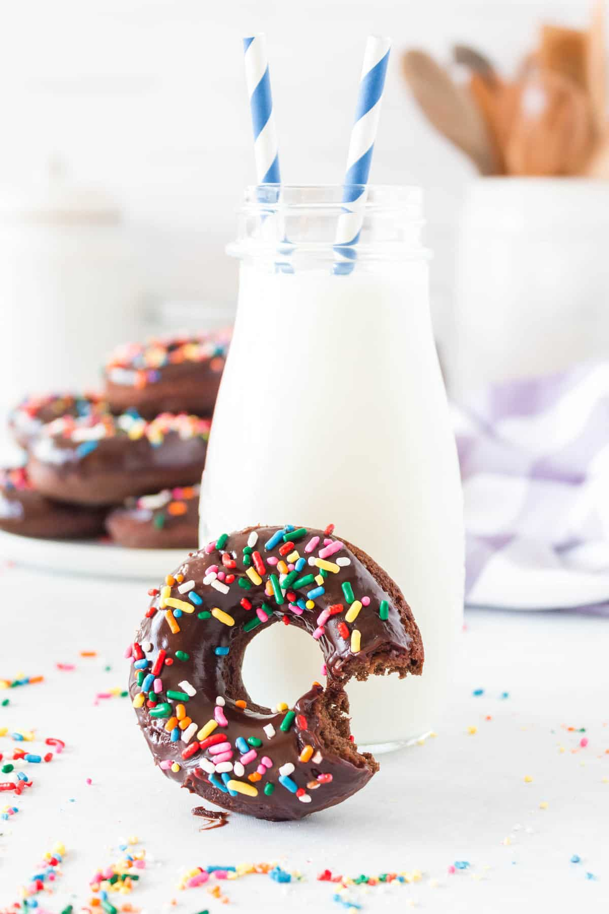 Chocolate sprinkle donut with a bite out of it, in front of a glass bottle of milk.
