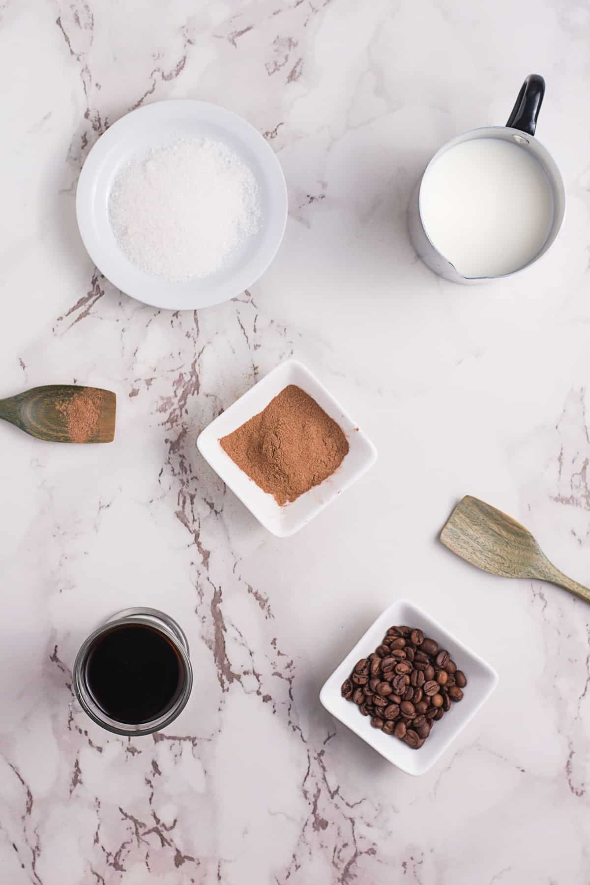 Overhead view of ingredients needed to make a cinnamon latte, including cinnamon, espresso, milk.