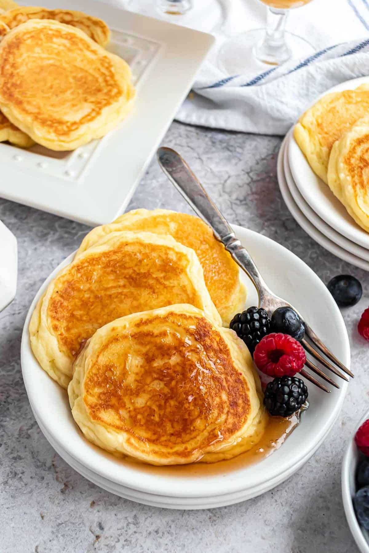 Three pancakes on a white plate with a fork, fresh berries, and syrup.