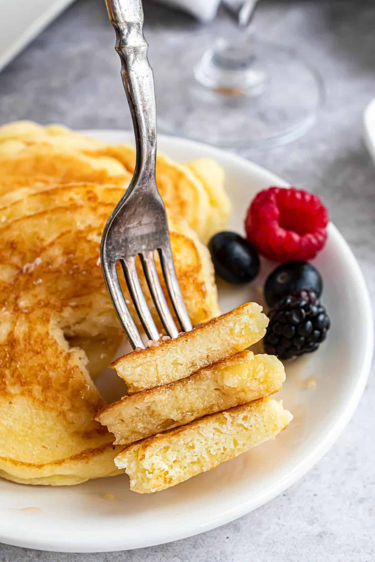 Three pieces of pancake on a fork, more in the background.