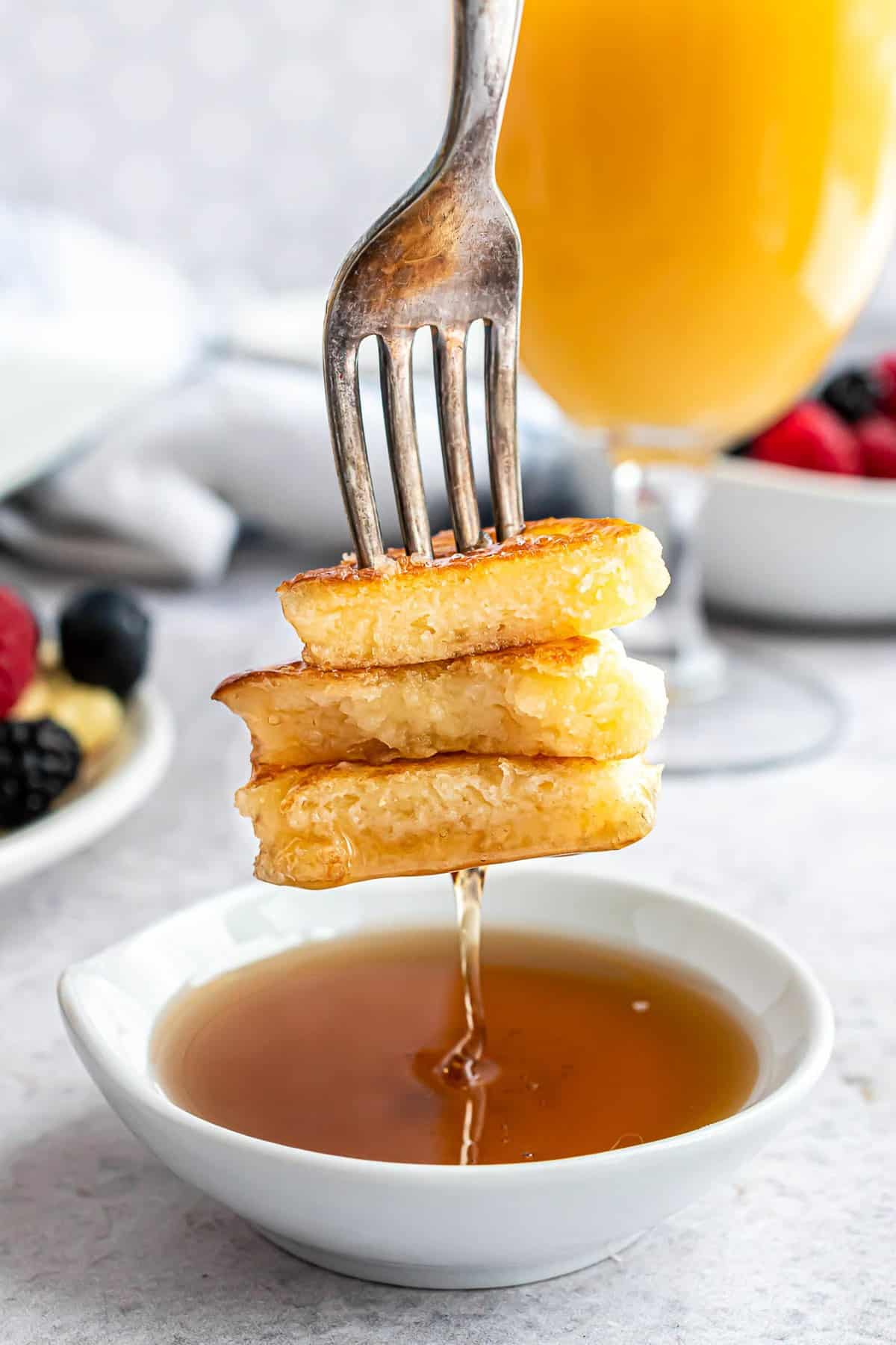 A fork dipping pancakes into a bowl of syrup.