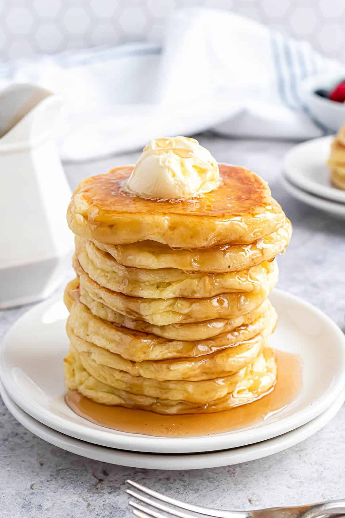 Tall stack of pancakes on a white plate, with butter and syrup.
