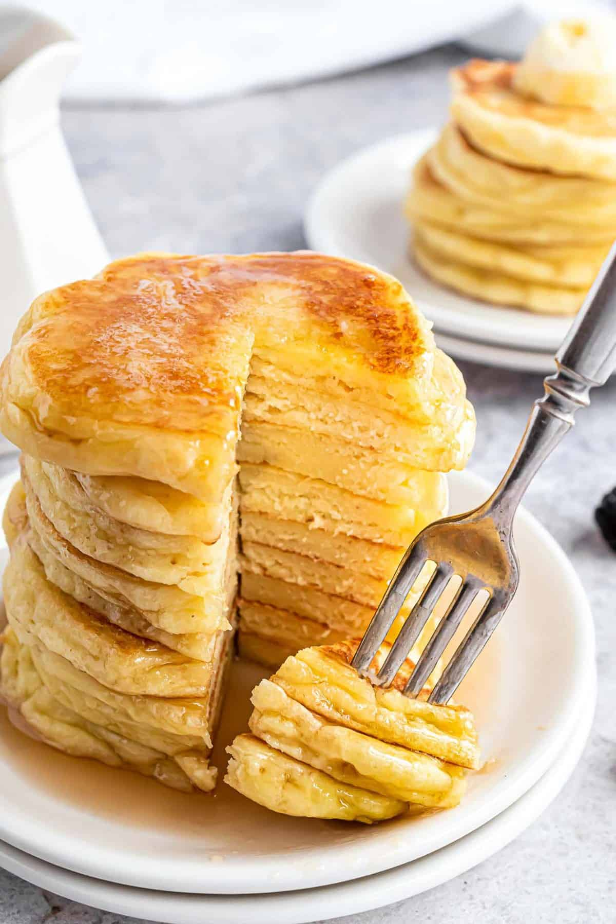 Large stack of pancakes being cut into with a fork.