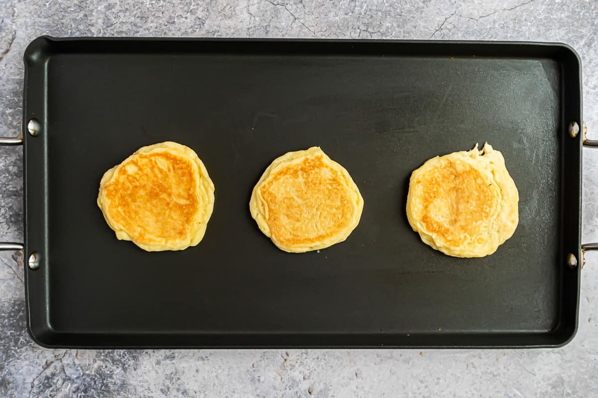 3 cooked pancakes on a black griddle.