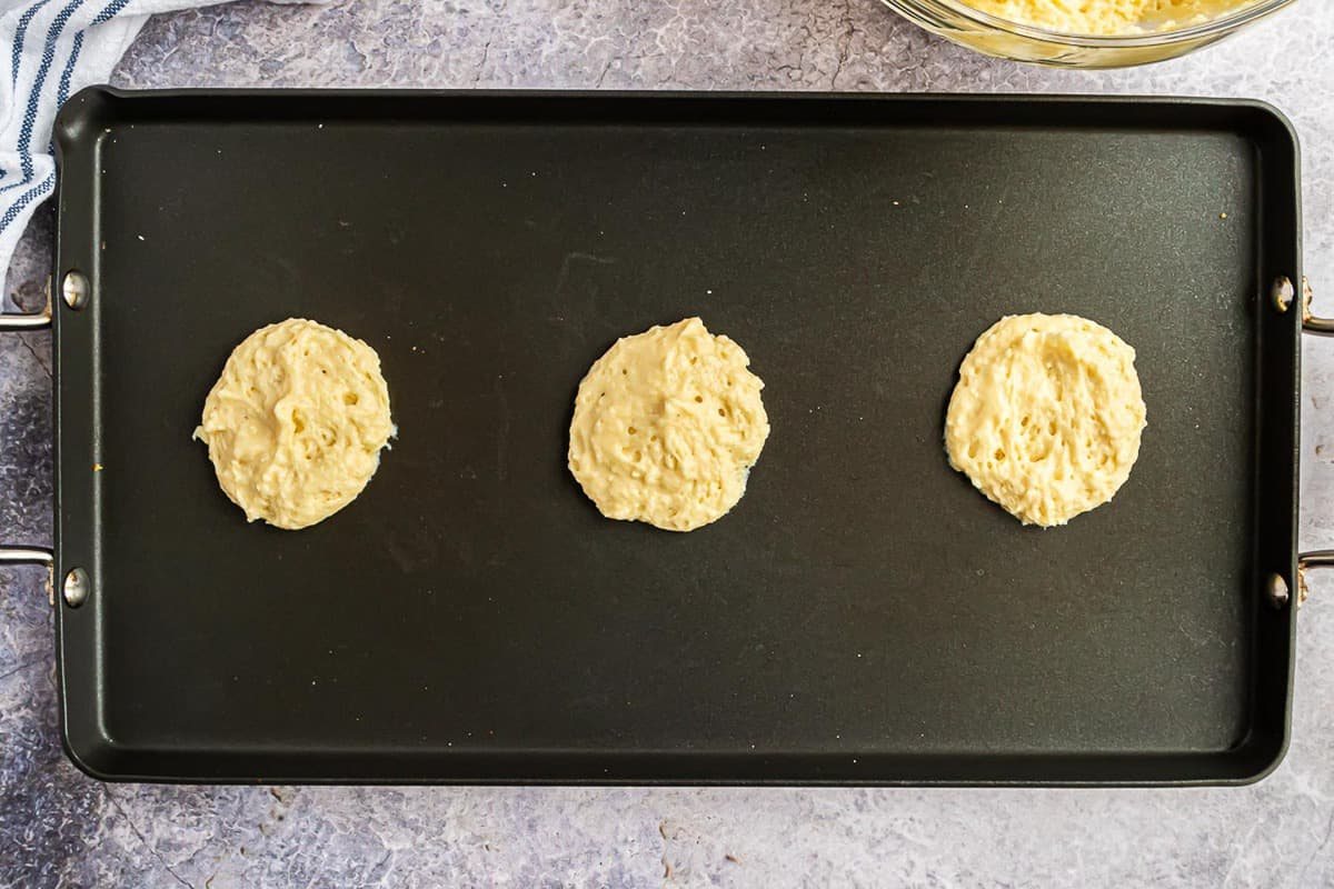 Three pancakes, halfway cooked, on a griddle.