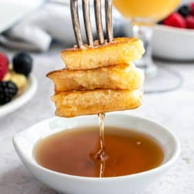 Pancakes on a fork, being dipped into syrup.