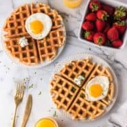 Overhead view of waffles topped with eggs, goat cheese, and chives.
