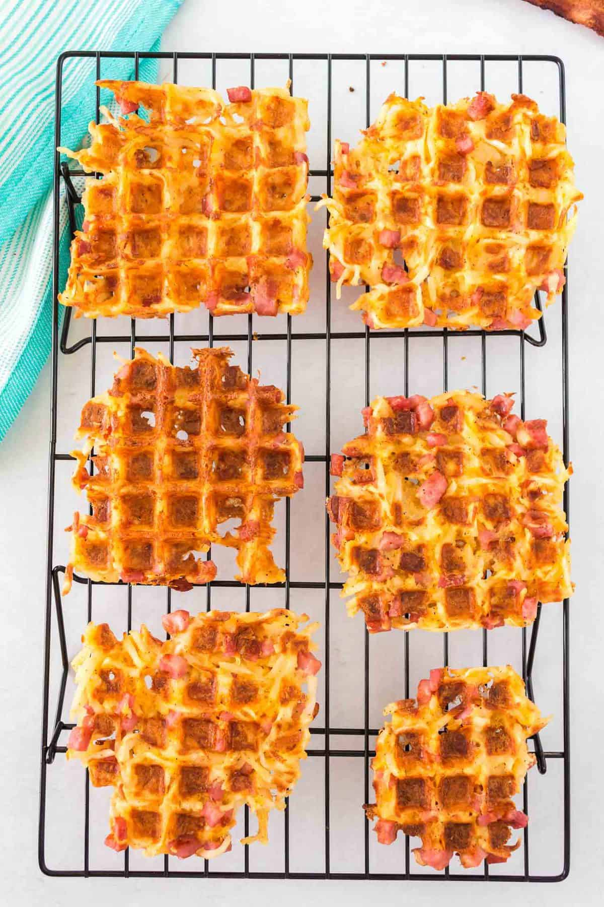 Overhead view of waffles made with hash browns, ham, and cheese.