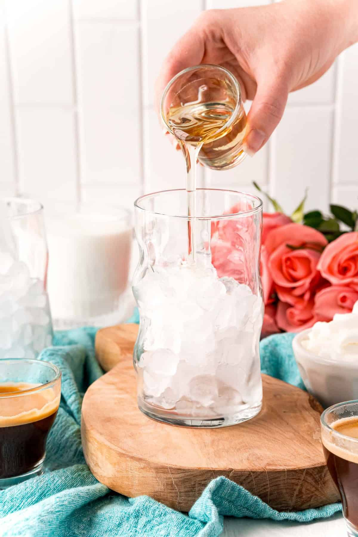 Syrup being poured into a glass with ice.
