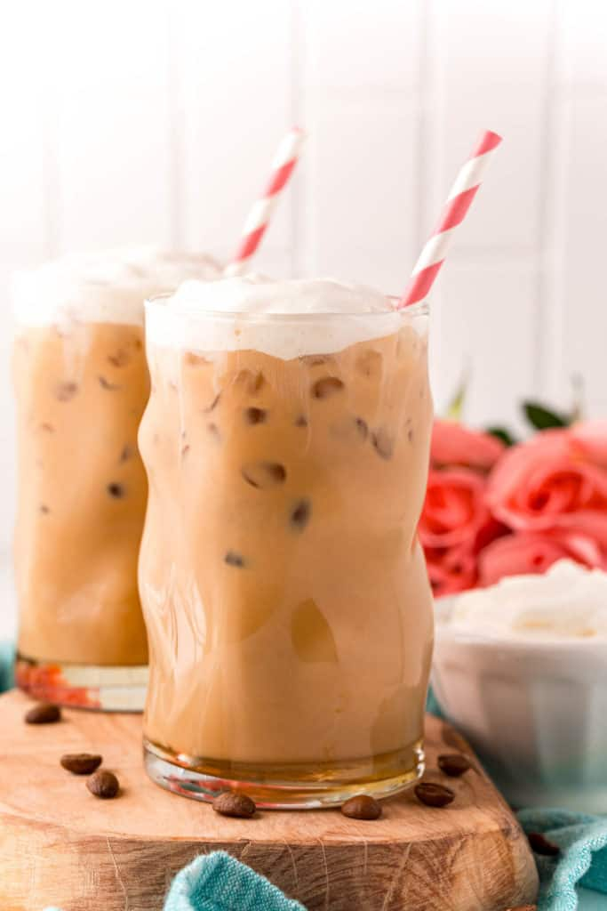 Two iced coffees topped with whipped cream.
