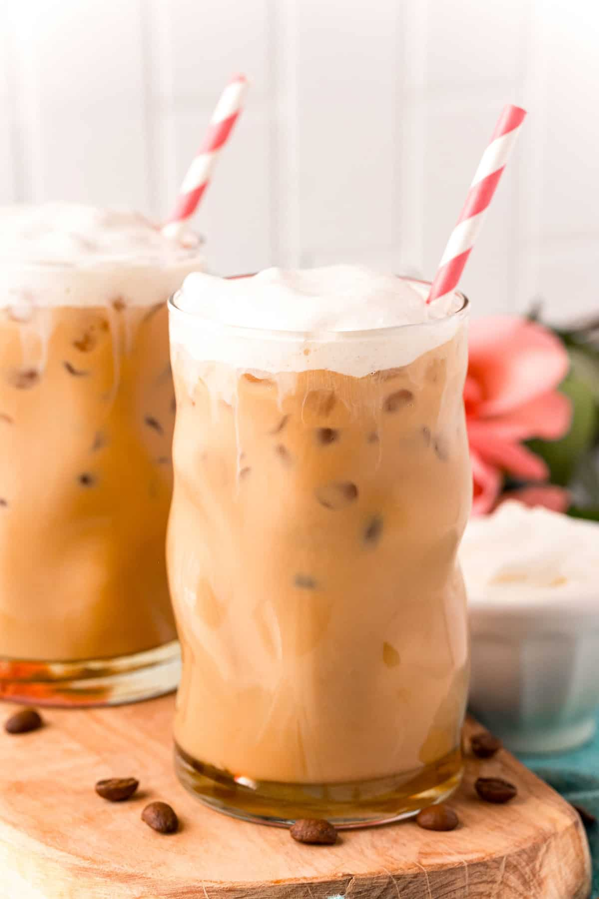 Two iced coffee drinks topped with whipped cream, with striped straws.