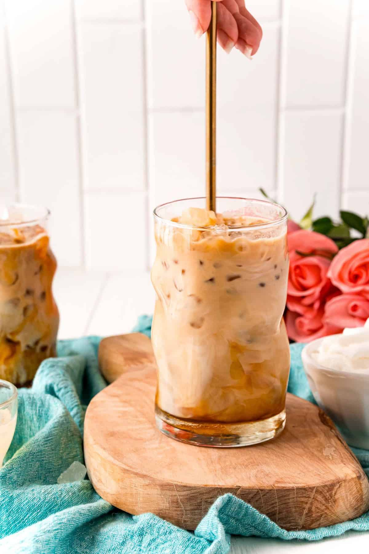 Iced latte being stirred with a spoon.