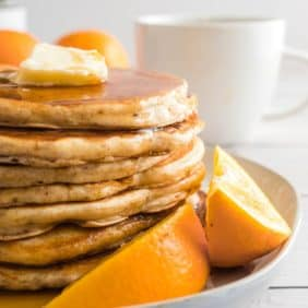 Pancakes stacked on a plate, with orange wedges.