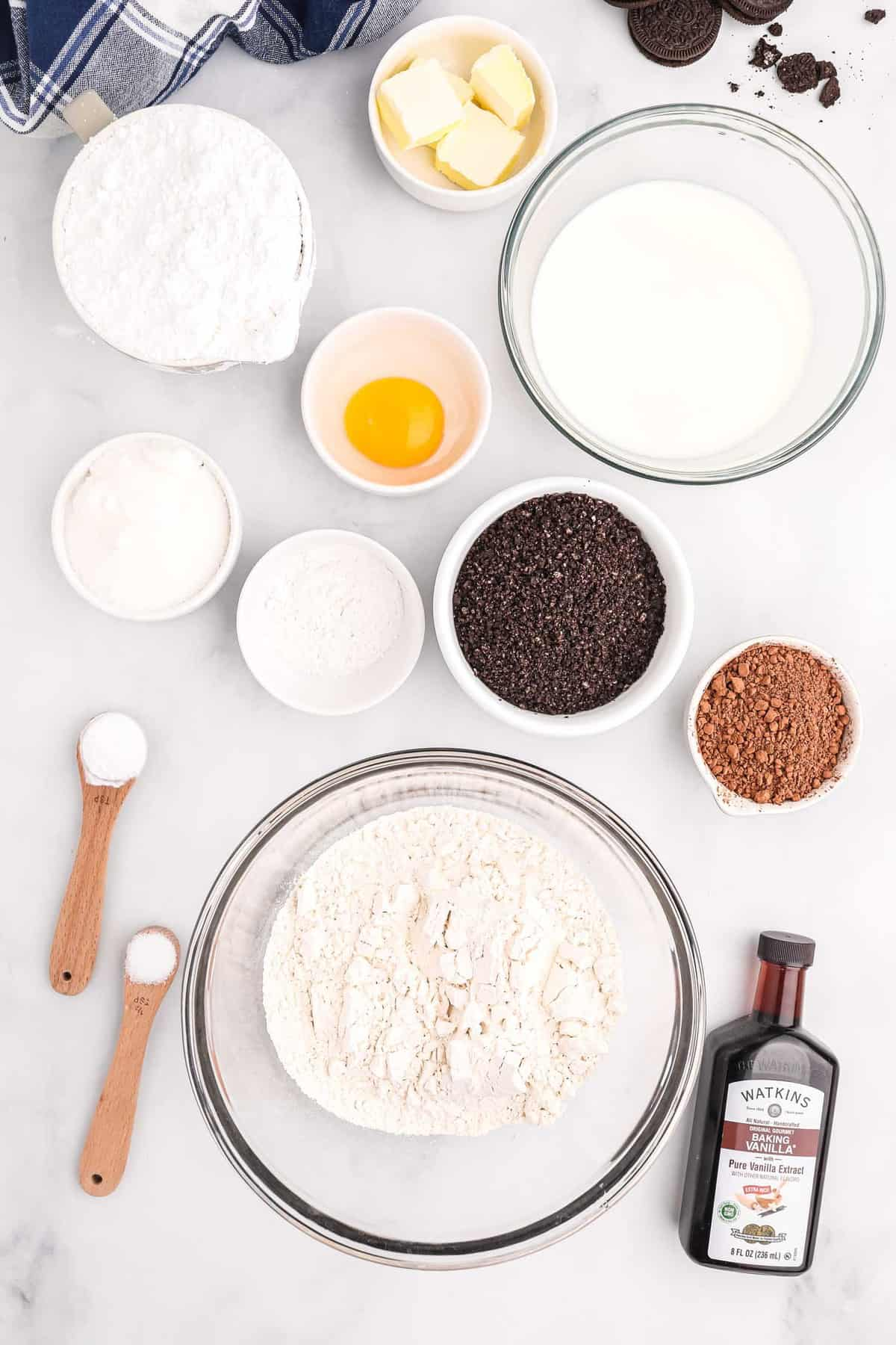 Overhead view of ingredients in bowls, including flour, cocoa powder, egg, butter, and more.