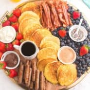 Overhead view of pancakes and other breakfast items decoratively placed on a board.