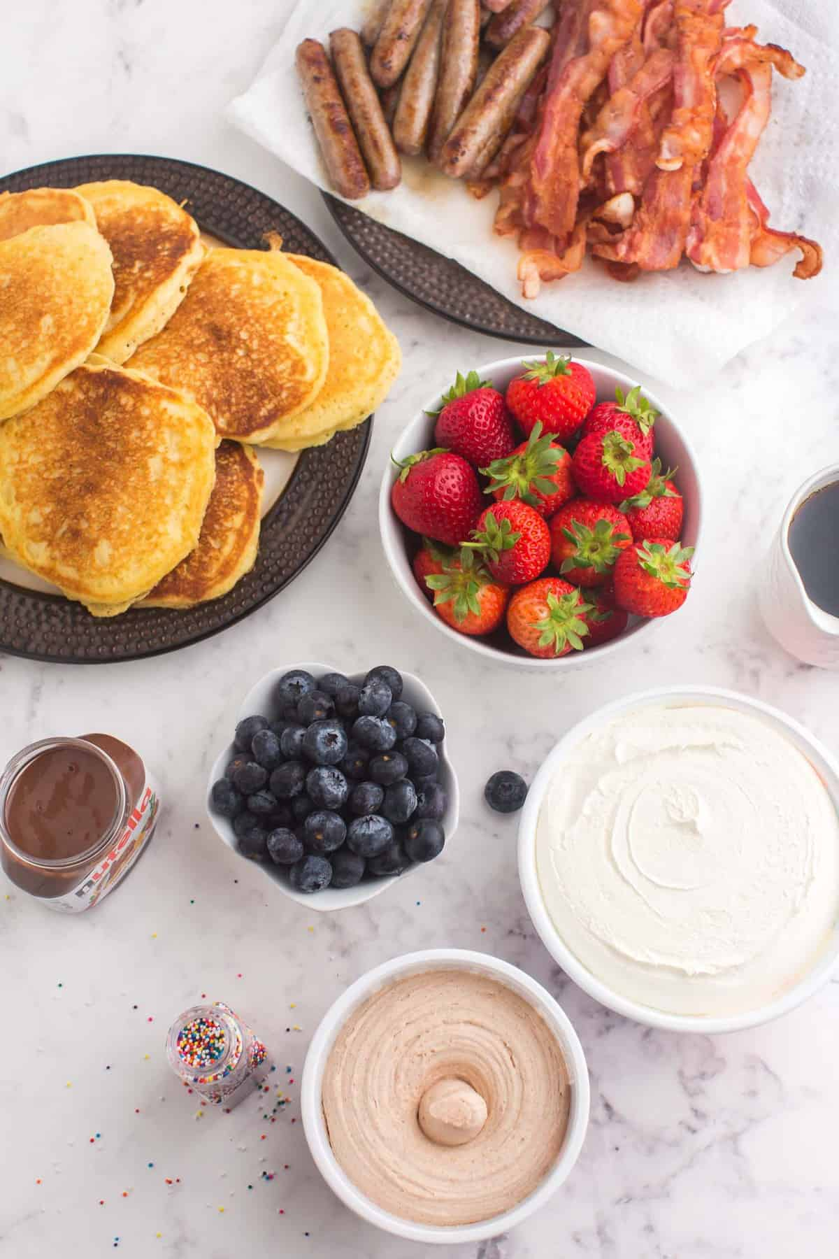 Ingredients in separate bowls and plates, pancakes, fruit, toppings, and breakfast meats.