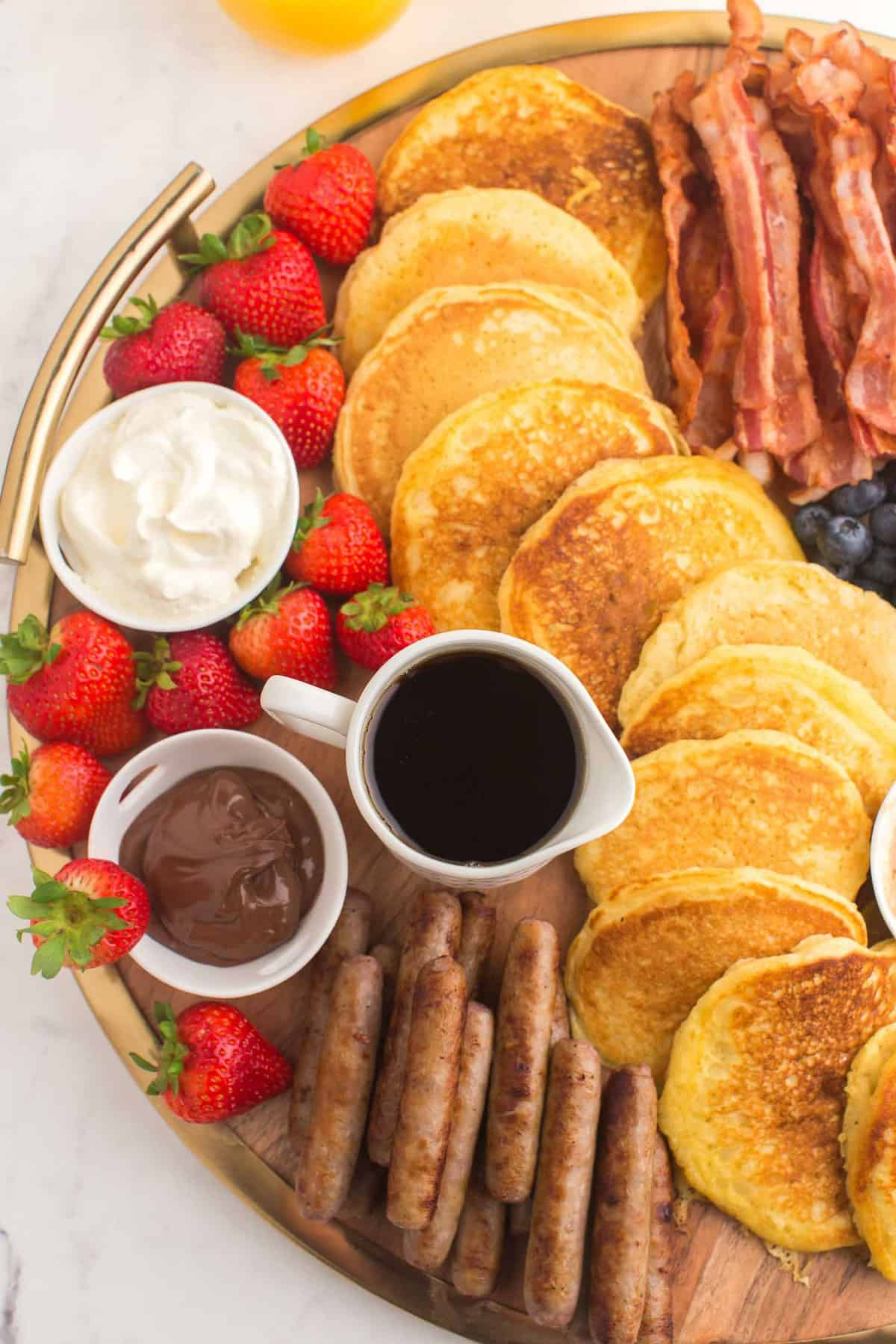 Pancakes, bacon, syrup, sausage, and strawberries on a board.