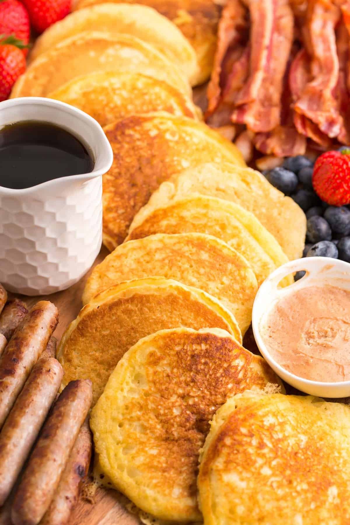 Close up of pancakes in a decorative pattern surrounded by other breakfast items.