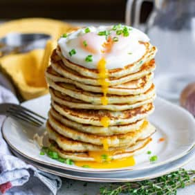 Tall stack of pancakes with a runny fried egg on the top.