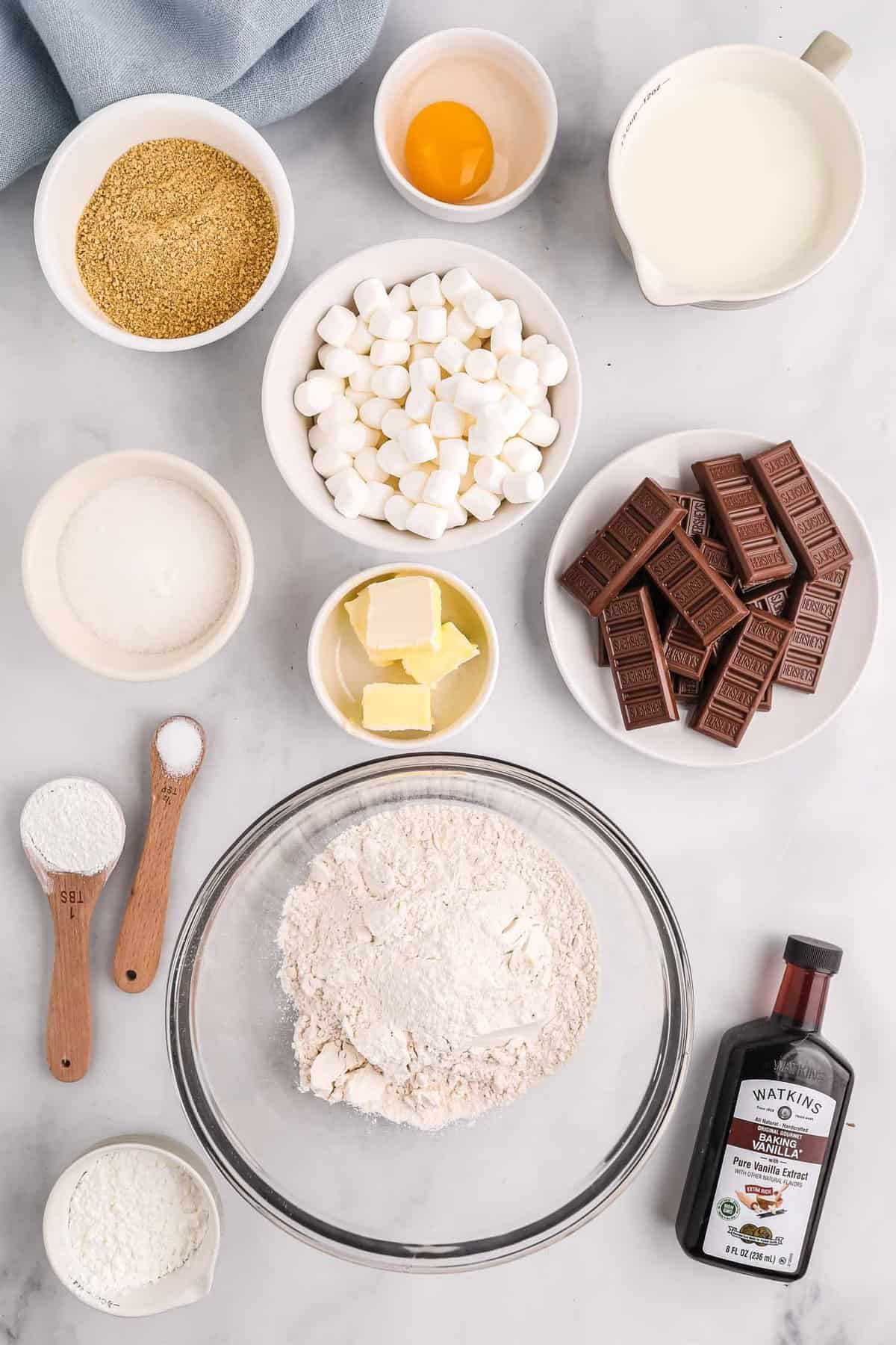 Overhead view of ingredients needed to make sheet pan pancakes, including chocolate bars, marshmallows, and graham cracker crumbs.