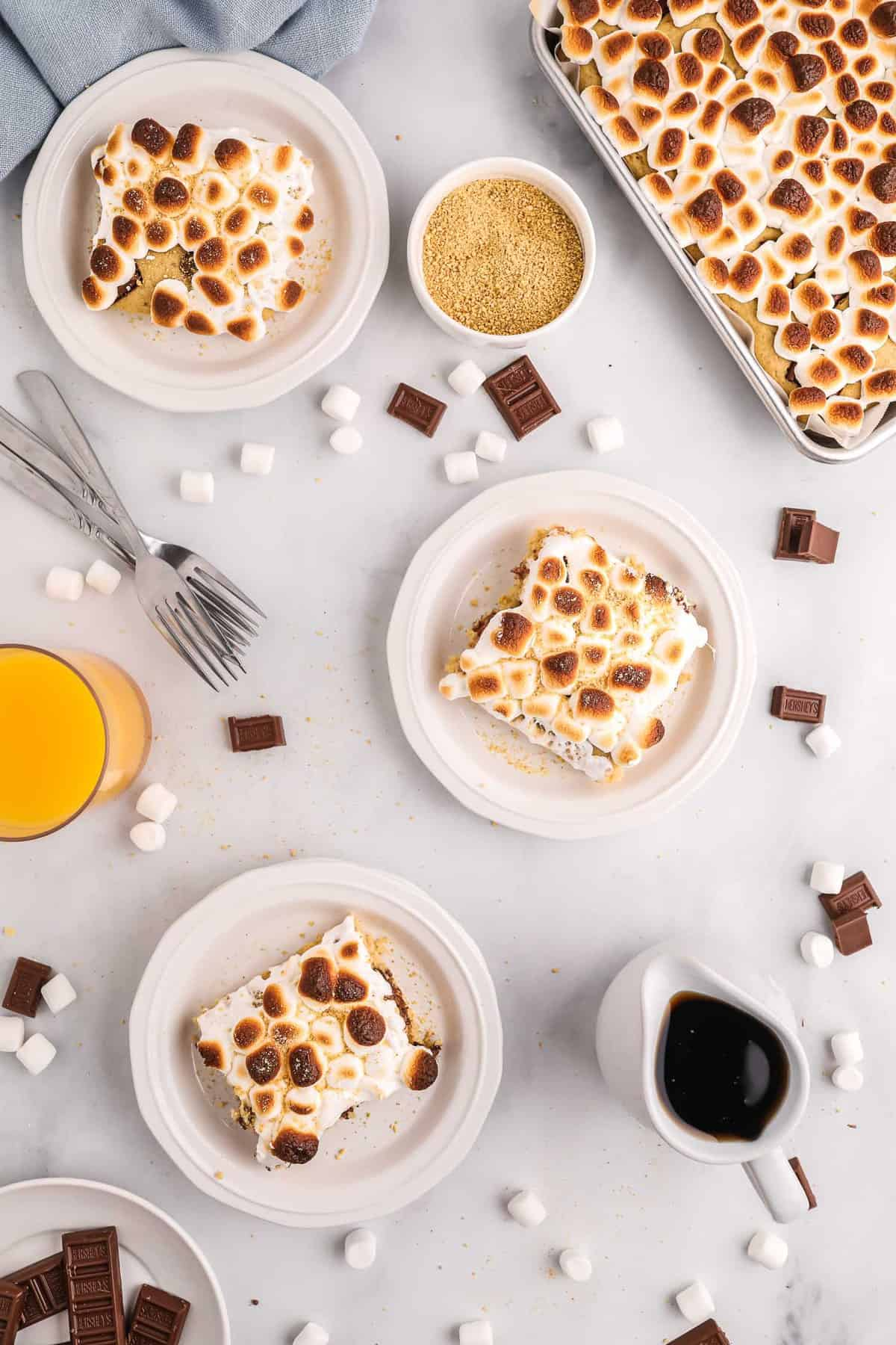 Overhead view of three plates of s'mores pancakes with a sheet pan of more also visible.