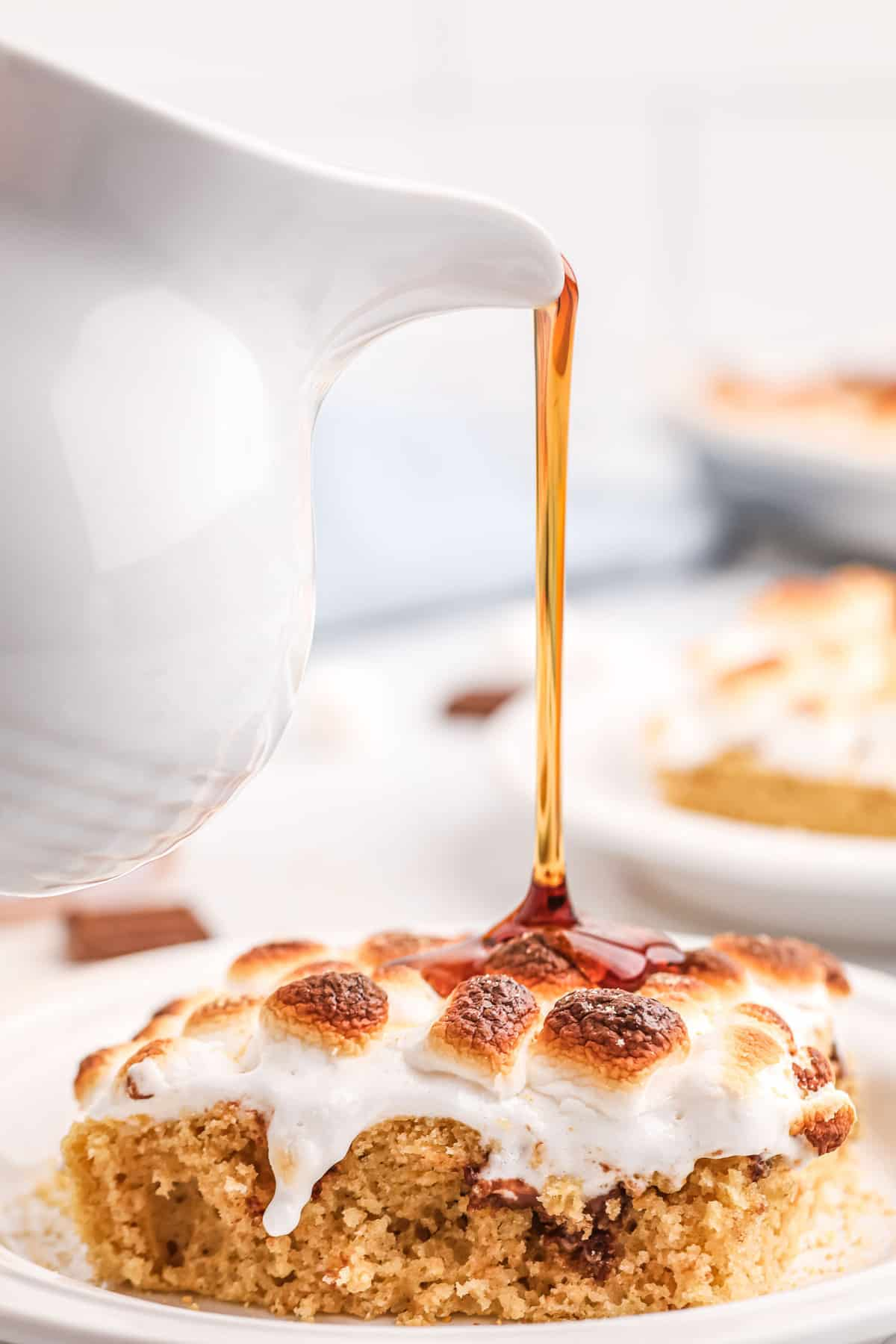 Syrup being poured on top of a marshmallow topped pancake.
