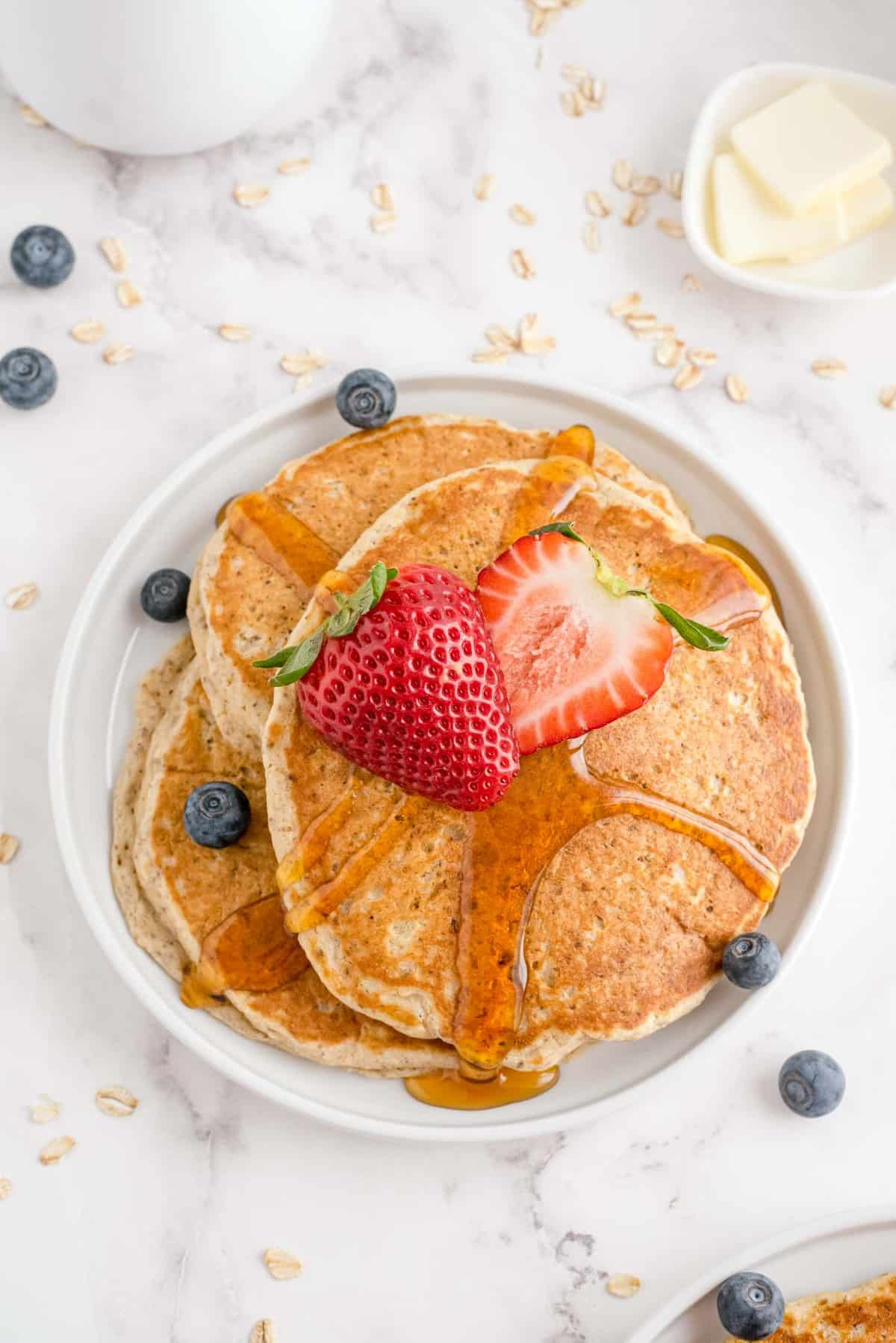 Pancakes on a white plate with strawberries and blueberries.