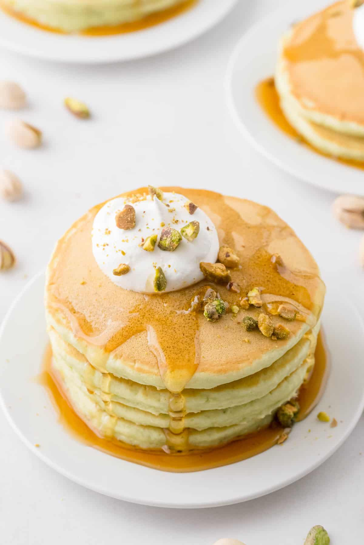 Pancakes topped with syrup, whipped cream, and pistachios.