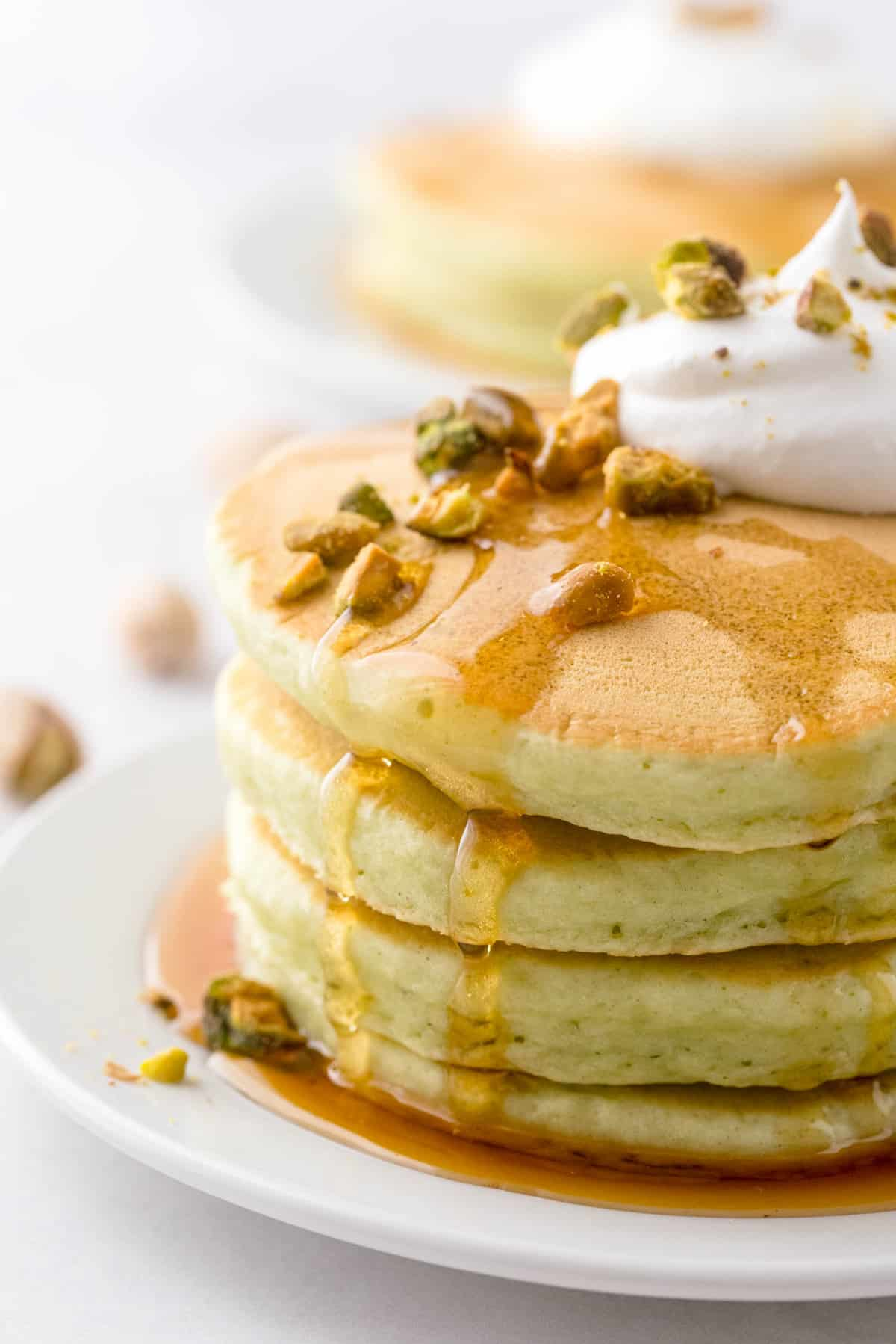 Short stack of light green pancakes, dripping with syrup and topped with pistachios.