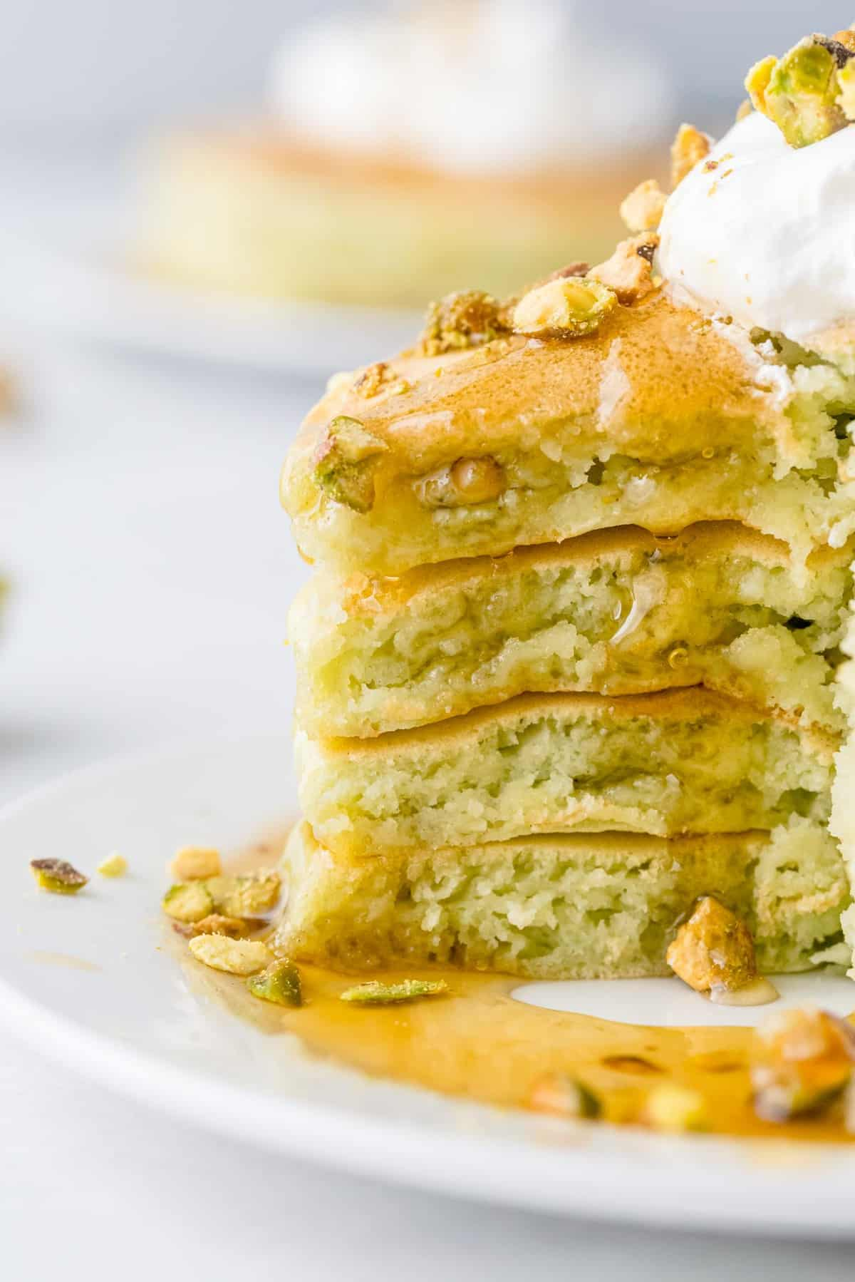 Close up of syrup dripping down a stack of cut light-green pancakes.