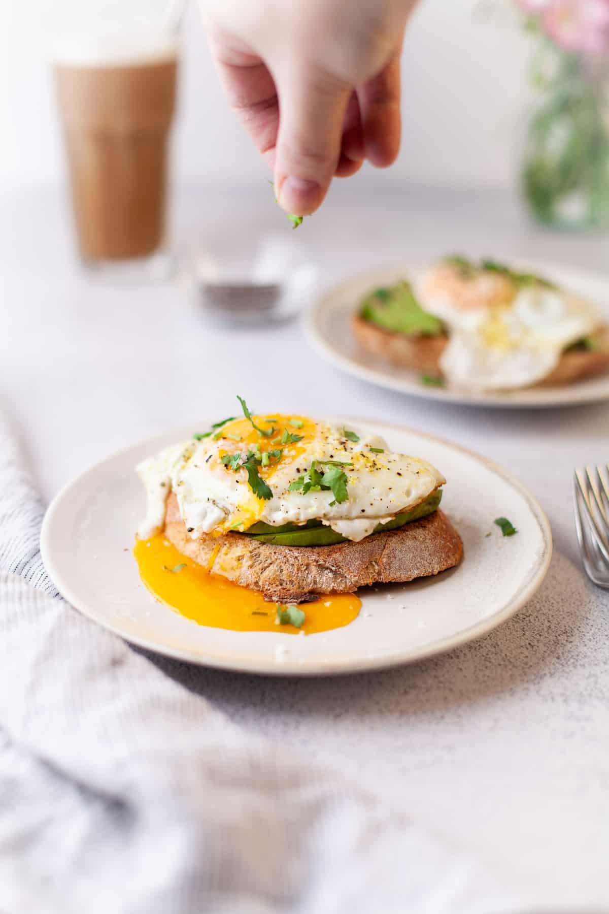 Egg topped avocado toast being sprinkled with herbs.