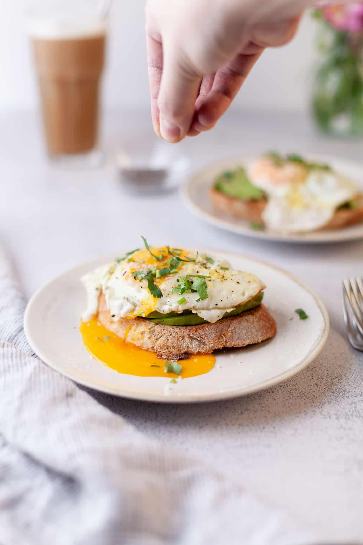 A hand sprinkling herbs on avocado toast with egg.