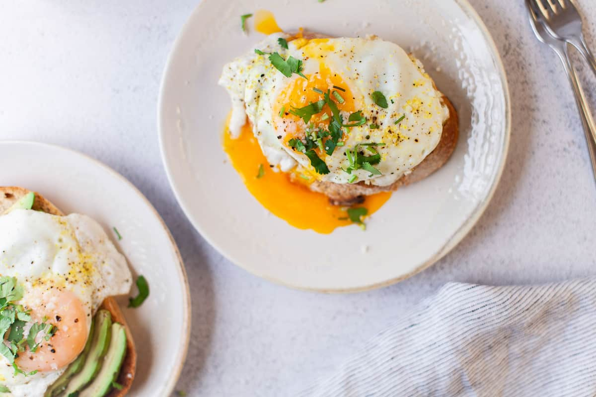 Overhead view of a runny egg on top of avocado toast.