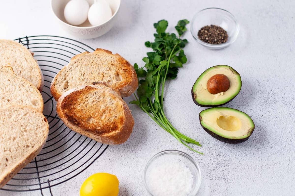 Toast, herbs, avocados, eggs, and seasonings on a grey surface.
