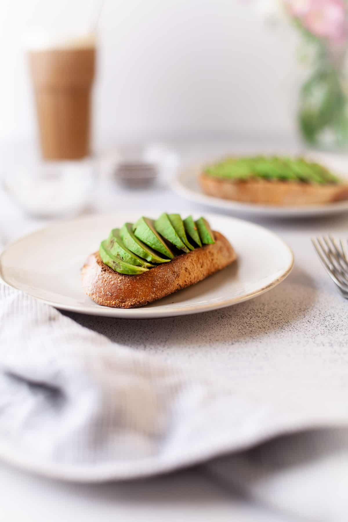 Slices of avocado on top of toast on a white plate.