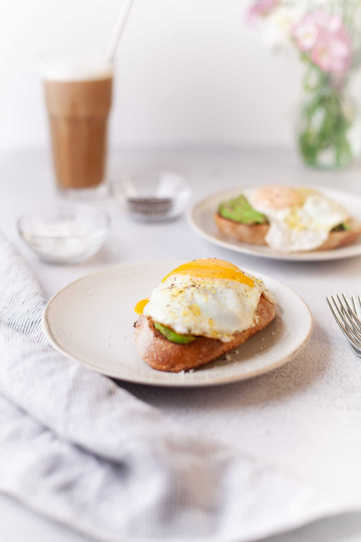 White tabletop with two egg topped avocado toasts, coffee, and a vase of flowers.