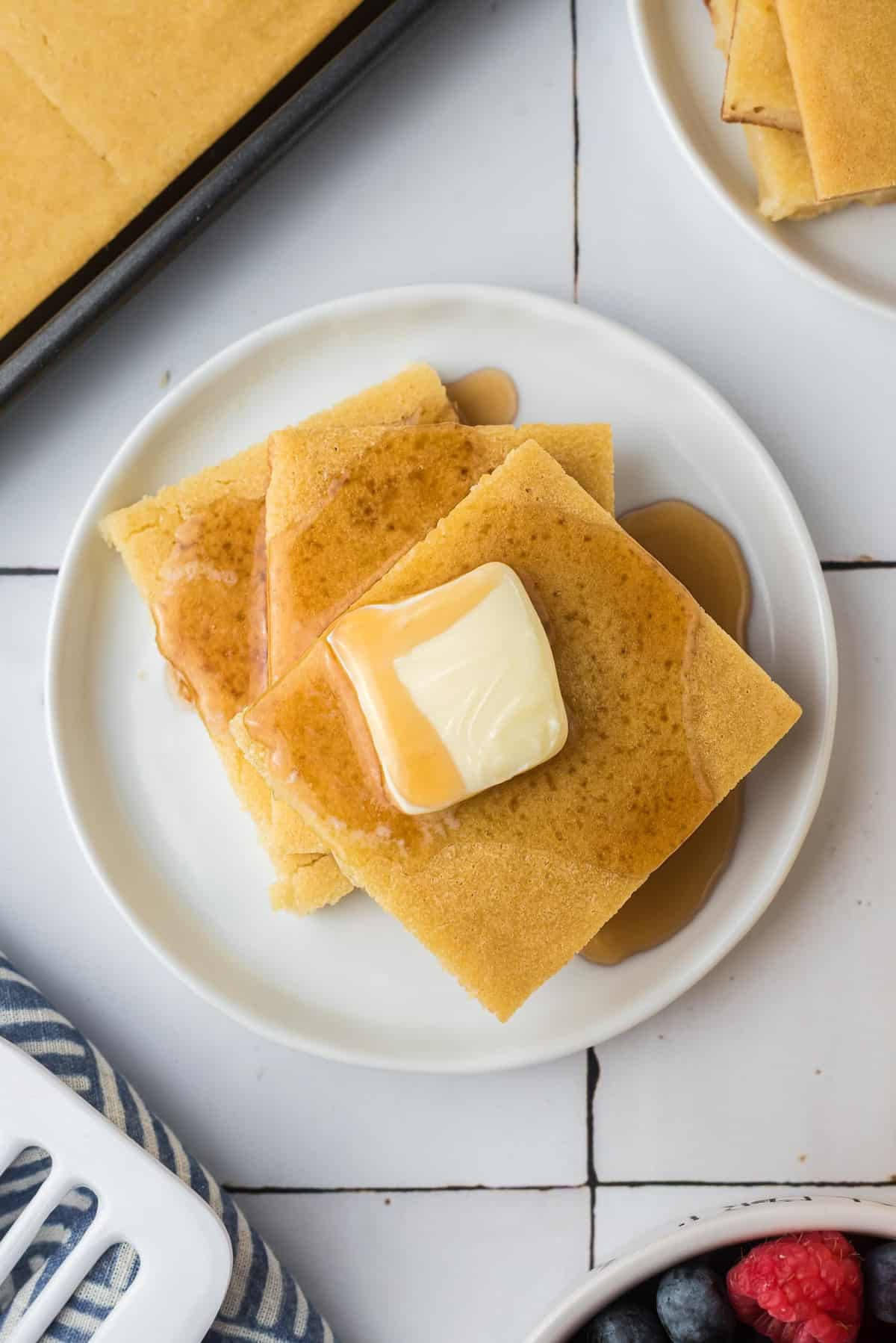 Close up overhead view of square pancakes with butter and syrup.