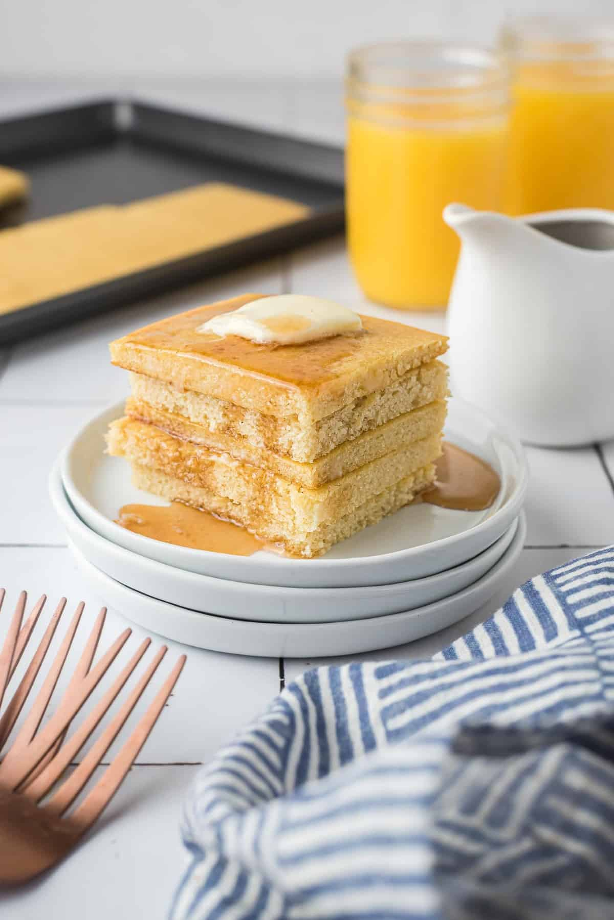 Stack of square cut pancakes on a white plate with butter and syrup.