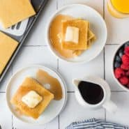 Overhead view of square pancakes on two white plates with syrup and butter.