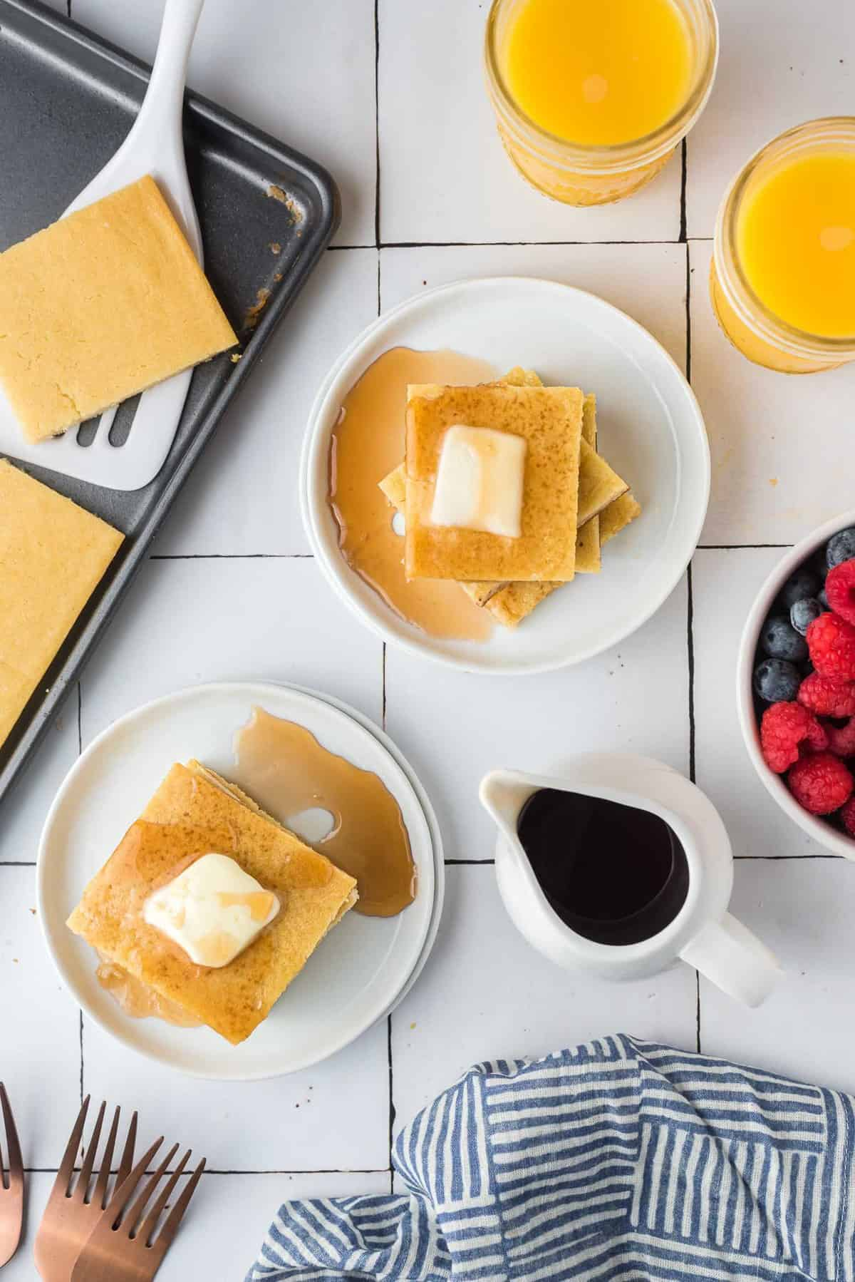 Overhead view of two plates of square pancakes, a sheet pan, fruit, and syrup.