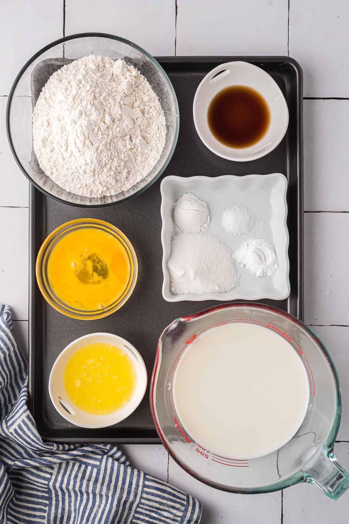 Ingredients on a black sheet pan: flour, eggs, vanilla, milk, butter, baking soda, baking powder, salt.