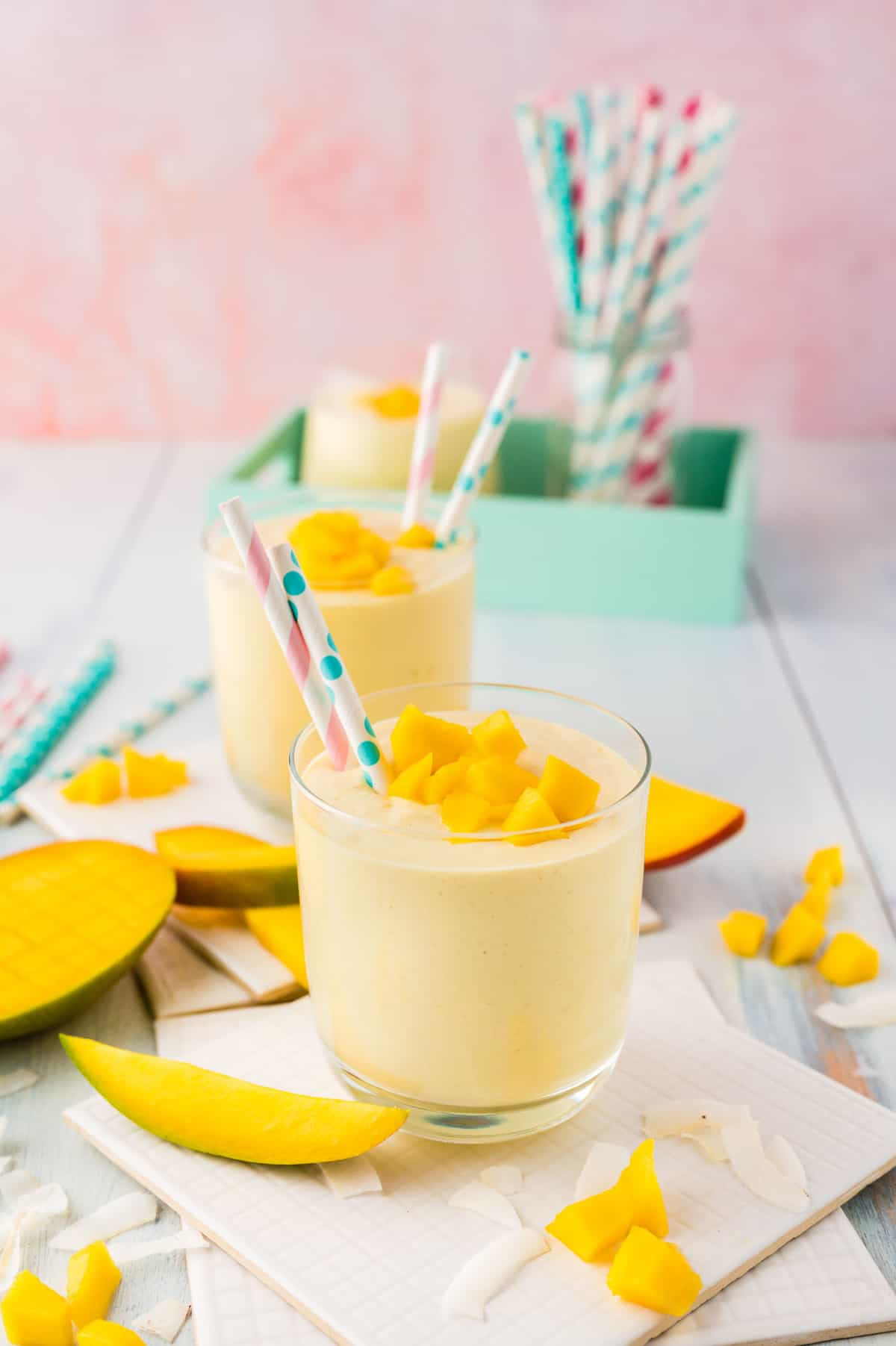 Two small glasses filled with mango smoothies, fun straws in drinks and in background.