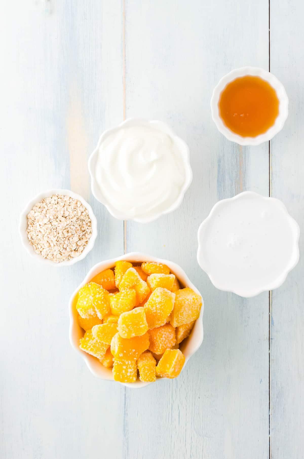Overhead view of bowls of ingredients: mango, coconut milk, yogurt, milk, and honey.