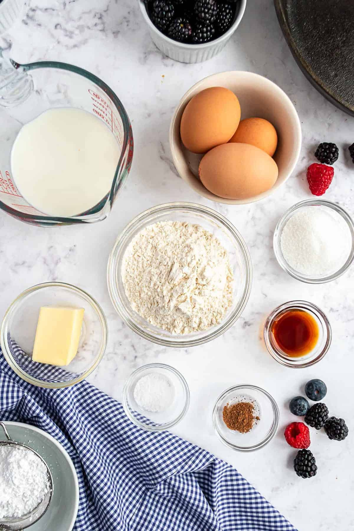 Overhead view of ingredients: flour, milk, eggs, vanilla, butter, and more.